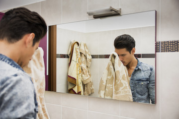 Reflection of Man Drying Face with Towel in Mirror