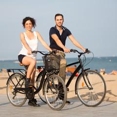 Zwei Personen fahren Rad auf einem Citystrand