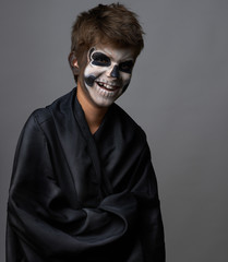 Teen with make-up of skull in black cloak laughs