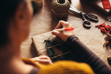 Woman writing on modern Christmas gifts presents at home