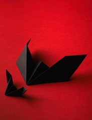 Origami bat on a red background