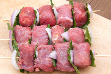 Skewers of meat on cutting board