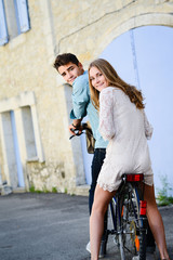 happy young couple teenager sightseeing together summer bicycle