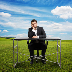 sad businessman sitting at table