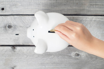 Asian boy hand dropping a coin into white piggy bank  against wo