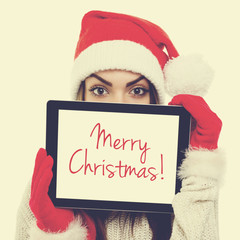 Cute Santa girl showing digital tablet with Merry Christmas text