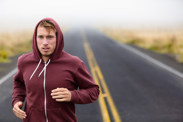Athlete man running training on road in fall