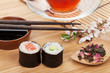 Sushi maki set, herbal tea and sakura branch