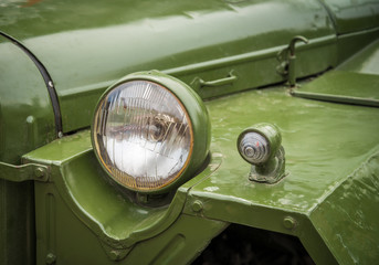Headlight on a old military vehicle, closeup. Selective focus.