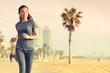 Running woman jogging on beach boardwalk