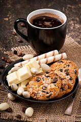 Cup of coffee with white chocolate, almonds and cookies