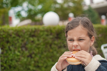 little caucasiangirl eating burger, looking down