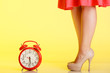 canvas print picture - Sexy female legs in high heels and red clock.