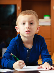Blond boy child kid with pen writing on piece of paper. At home.