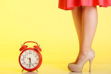 Sexy female legs in high heels and red clock.