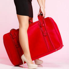 Side view woman legs with red suitcase on pink background