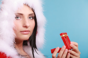 woman wearing santa claus costume holds gift box on blue