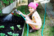 Kid girl watering plants in the garden