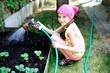 Kid girl watering plants in the garden