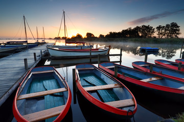 boats and yachts on lake at sunrise