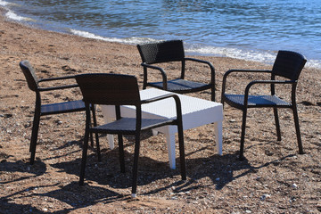 Cafe on the beach: wicker table and chairs by the sea.