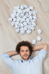 Young Man Lying On Floor With Crumpled Papers