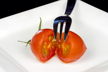 Little fork and small tomato