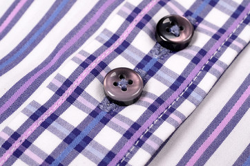 Close-up of buttons on a striped purple shirt.