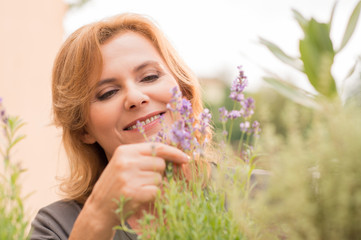 Mature Woman Looking At Flowers