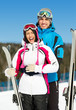 Half-length portrait of two hugging alps skiers with skis