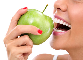 closeup of the face of a woman eating a green apple