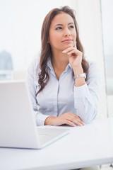 Pretty businesswoman thinking at her desk