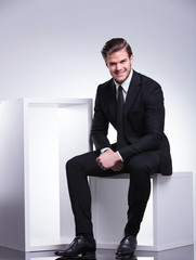 young business man smiling for the camera while sitting