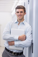 Portrait of a smiling technician holding a laptop