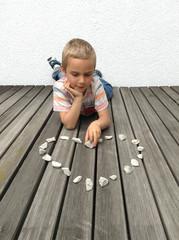 Junge legt ein Herz aus Steinen