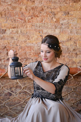 Beautiful young woman wearing long dress, holding lamp