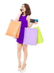 beautiful woman with shopping bags talking on phone