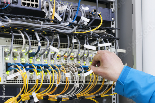 Leinwandbild Motiv Man connecting network cables to switches