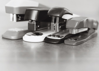 four staplers on wooden background.
