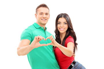 Young couple making a heart symbol with hands