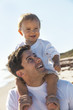 Father Man With Baby By Child on Shoulders at Beach
