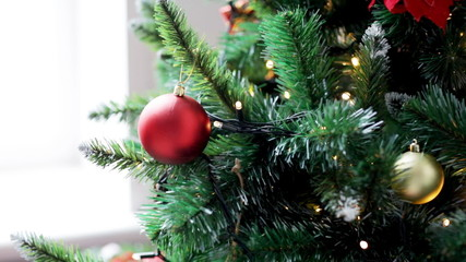 woman decorating christmas tree with ball