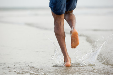 Man running barefoot in water