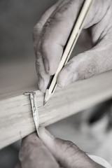 Sepia toned closeup of carpenter with pencil working on door