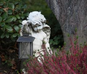 Engel mit Laterne auf herbstlichem Grab