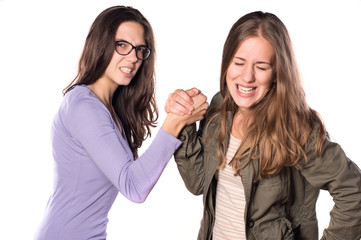 Two Young Girls Arm Wrestling and smiling
