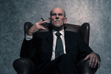 Cigar smoking senior businessman with gray beard wearing dark su