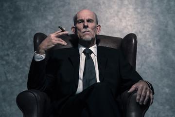 Cigar smoking senior businessman with gray beard wearing dark su