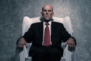 Bossy senior businessman with gray beard wearing dark suit and r