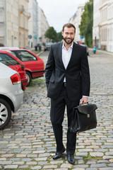 lächelnder mann auf dem weg ins büro